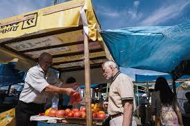 бабулька на базаре торгует овощами